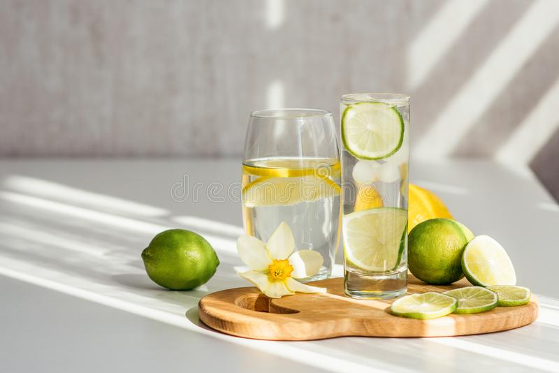 Two glasses of water with lemon and lime on a wooden board and a flower of narcissus. On a white table stock photo