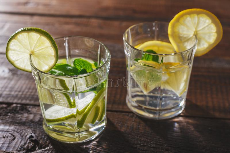 Two glasses of water, lemon, mint and ice on wooden table stock images
