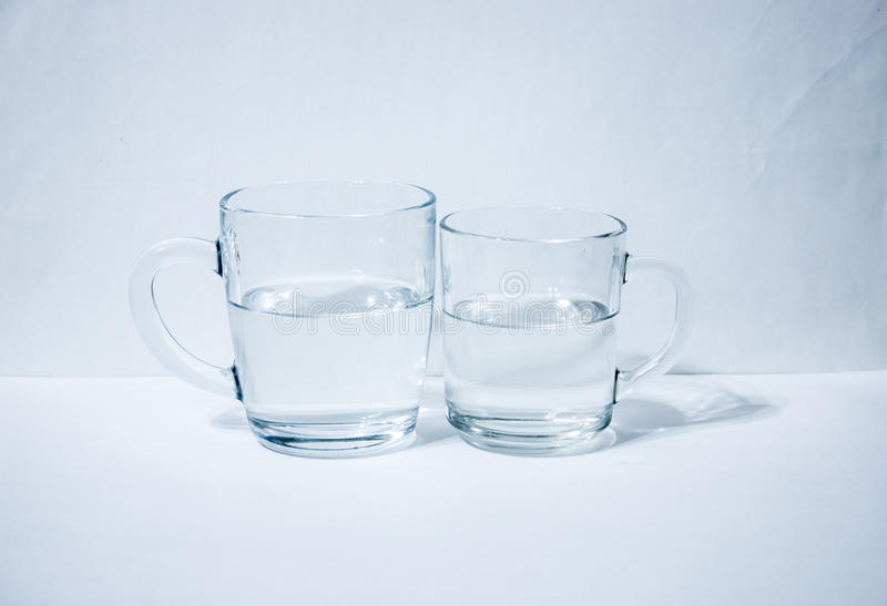 Two glasses of water. Light background stock photography