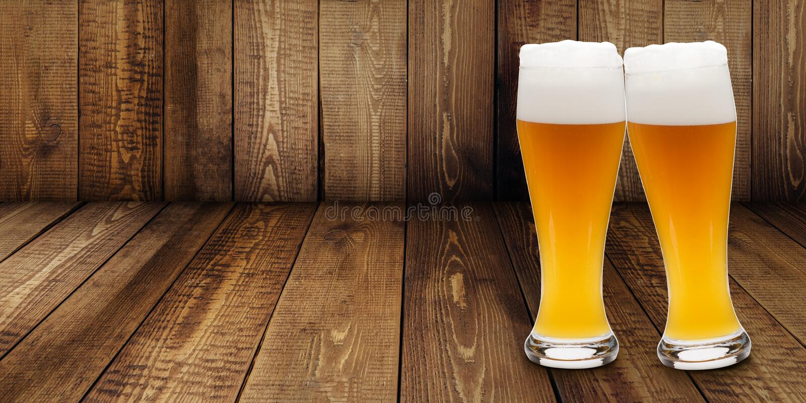 Two glasses of wheat beer making cheers on a wooden background royalty free stock photos