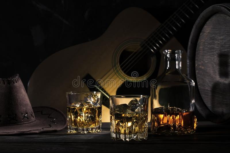 Two glasses of whiskey with ice and cowboy hat on wooden table stock photos