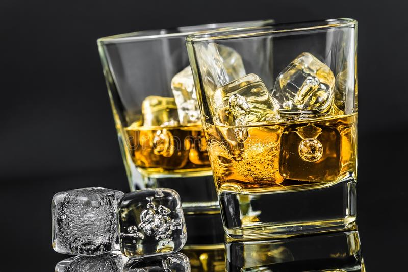 Two glasses of whiskey near ice cubes on dark background. Time of relax with whisky stock image