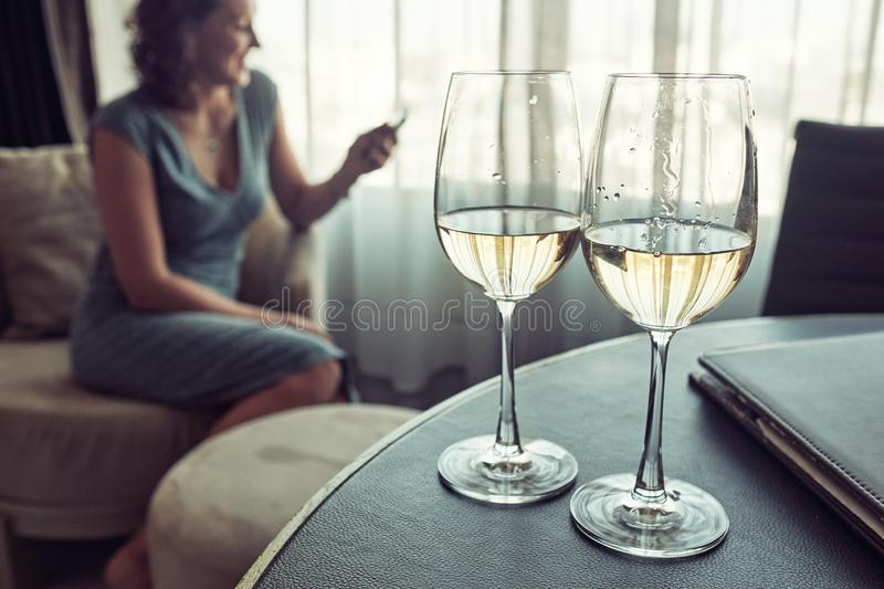 Two glasses of white vine on the table, on the background cheerful woman siting on the chair and using smartphone. royalty free stock photography