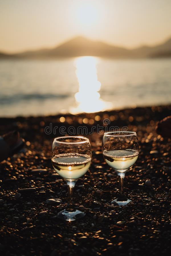 Two glasses with white wine on the beach at sunset stock image