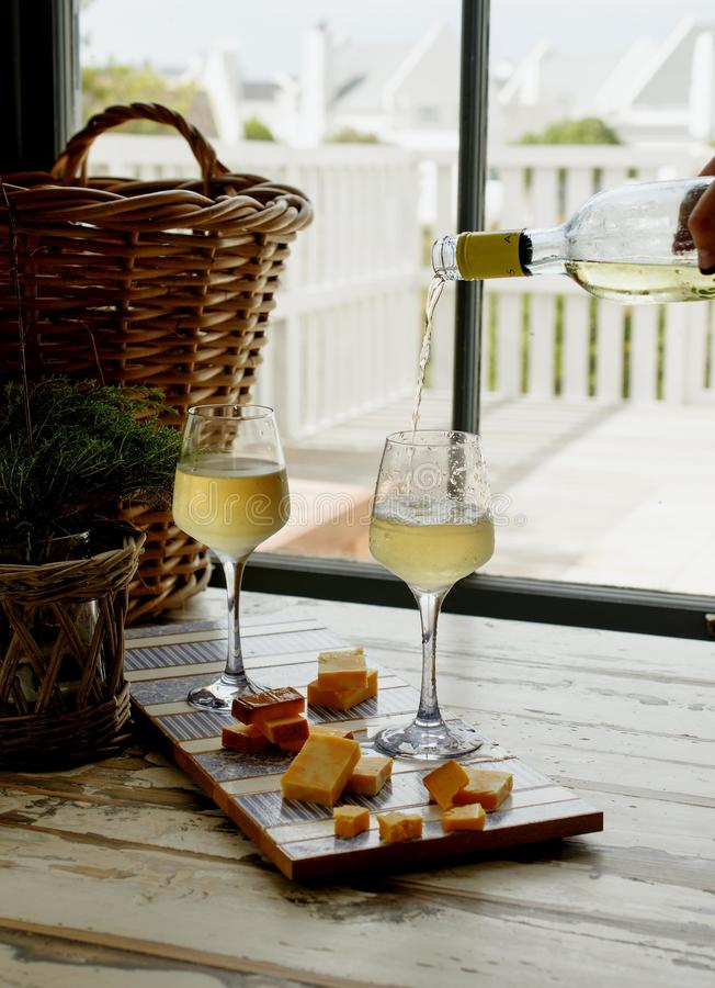 Two glasses of white wine with cheese, rustic, selective focus royalty free stock images