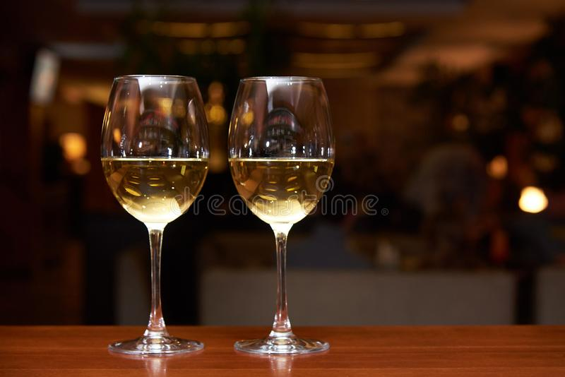 Two glasses of white wine with a reflection on the bar. Two glasses of white wine with reflection on the bar royalty free stock photo