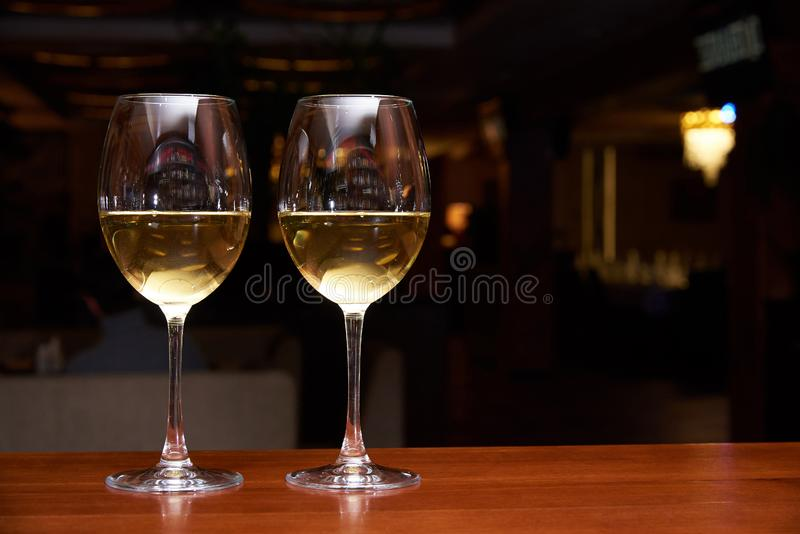Two glasses of white wine with a reflection on the bar. Two glasses of white wine with reflection on the bar royalty free stock image