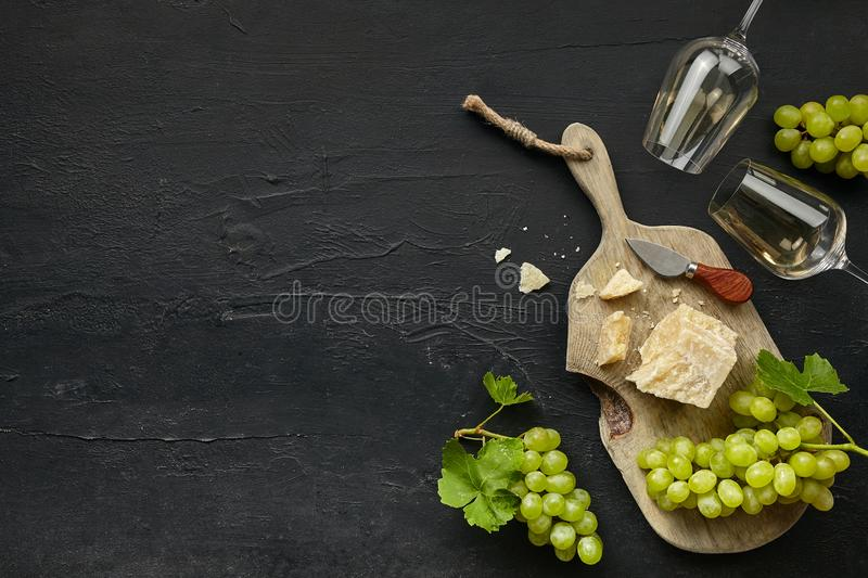 Two glasses of white wine and a tasty cheese plate on a wooden kitchen plate. stock image
