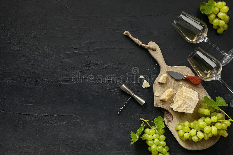 Two glasses of white wine and a tasty cheese plate on a wooden kitchen plate. stock photo