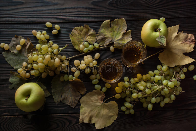 Two glasses with wine, apples and grapes on wooden surface royalty free stock photo