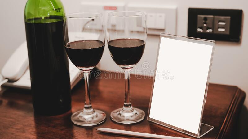 Two glasses of wine and wine bottle with phone on the wooden table royalty free stock photography