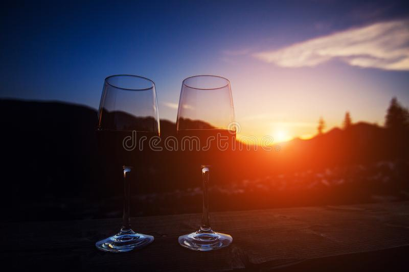 Two glasses of wine at sunset dramatic sky on mountain landscape background stock images