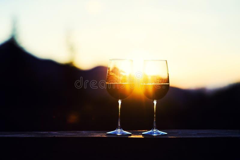 Two glasses of wine at sunset dramatic sky on mountain landscape background. Alcohol, anniversary, bar, beautiful, beverage, bottle, celebrate, celebration stock images