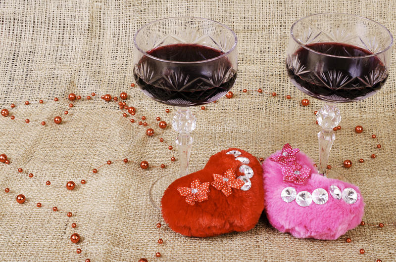 Two glasses of wine and two hearts close-up. royalty free stock image