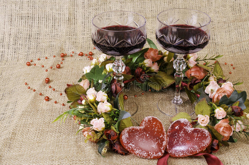 Two glasses of wine, a wreath of flowers and two hearts close-up. stock images