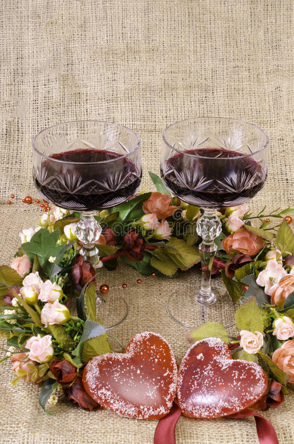 Two glasses of wine, a wreath of flowers and two hearts close-up. stock photography