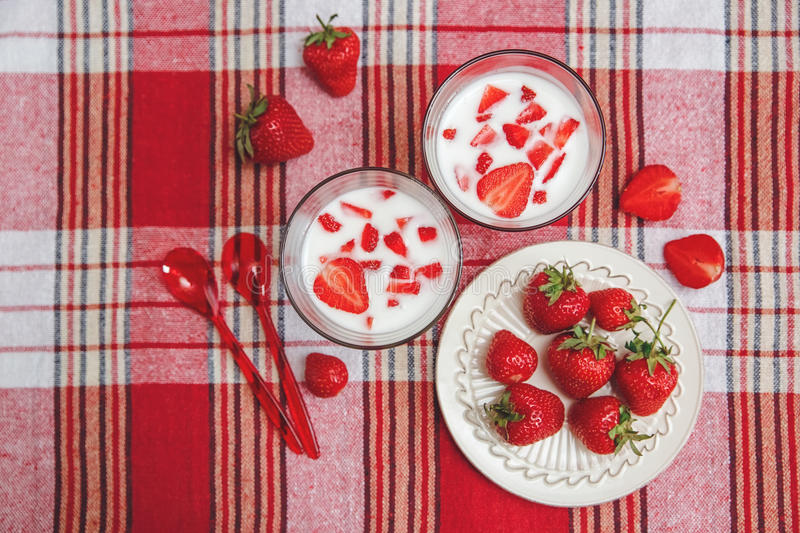 Two Glasses of Yogurt,Red Fresh Strawberries are in the Ceramic Plate with Plastic Spoons on the Check Tablecloth.Breakfast Organi royalty free stock image