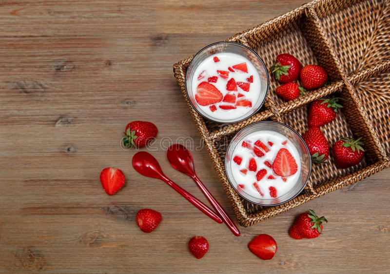 Two Glasses of Yogurt,Red Fresh Strawberries in the Rattan Box with Plastic Spoons on the Wooden Table.Breakfast Organic Healthy stock images