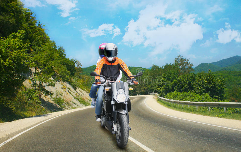 Two go on motorcycle on mountain road royalty free stock images