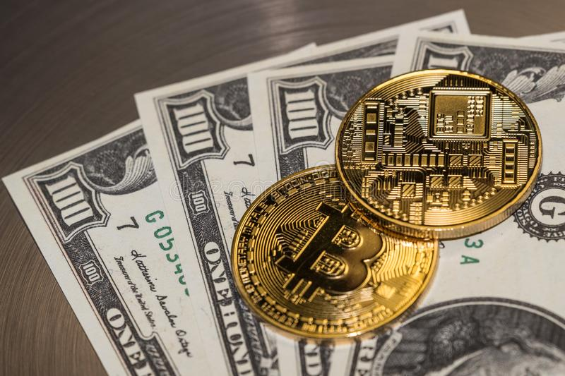 Two gold coins bitcoin lie on hundred dollar bills, photo close-up stock photography