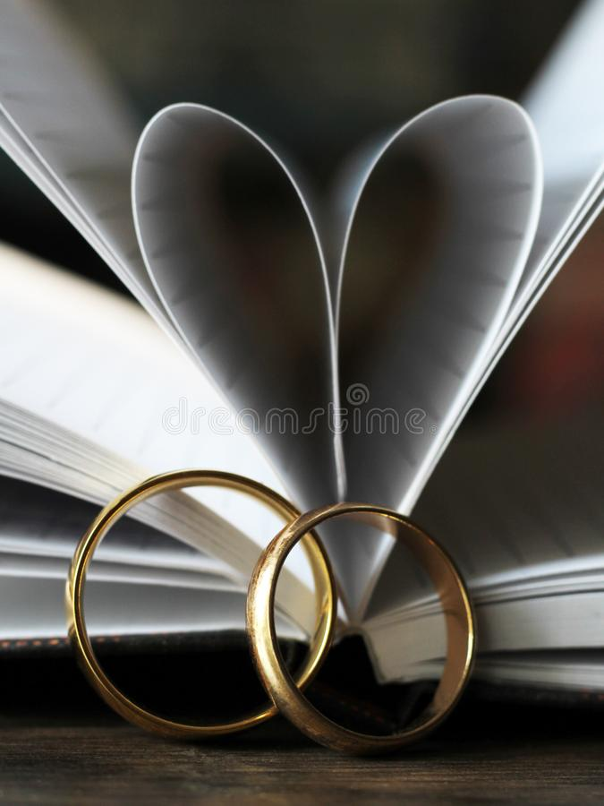 Two gold wedding rings and a heart made of paper pages stock photography