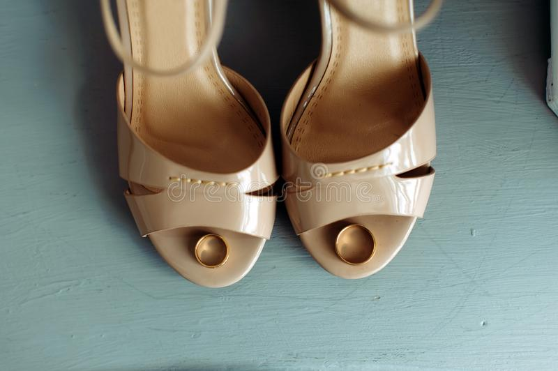Two gold wedding rings lie on beige bridesmaid shoes, vintage photo stock image