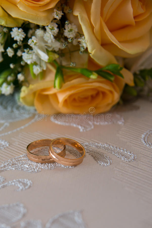 Two gold wedding rings lie on the table near the bouquet of orange roses and white flowers. stock photos