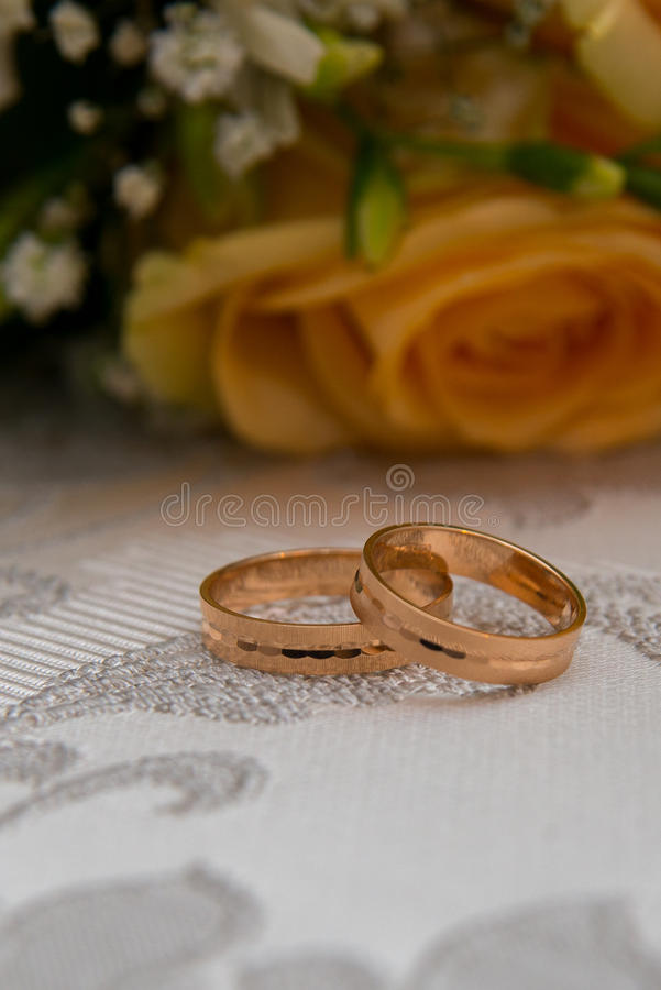 Two gold wedding rings lie on the table near the bouquet of orange roses and white flowers. stock photography