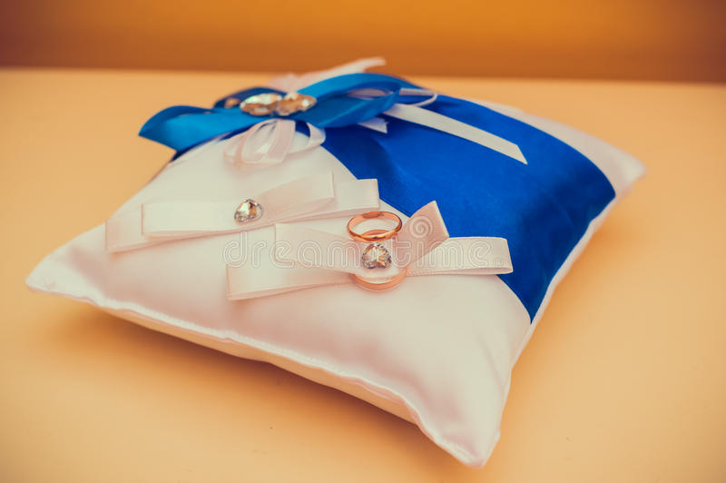 Two gold wedding rings lying on pillow royalty free stock photography