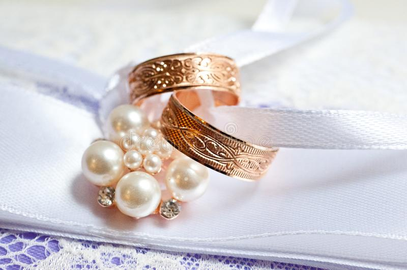 Two gold wedding rings with patterns on a beautiful cushion with decorations stock photography