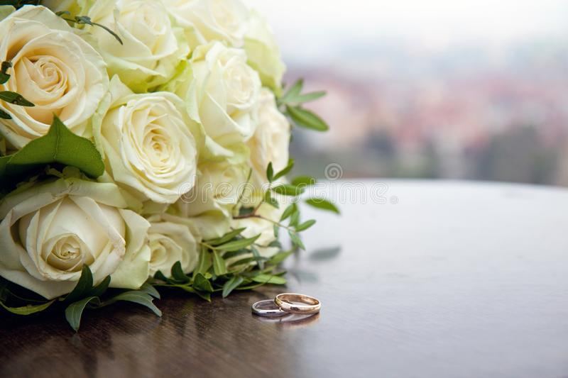 Two gold wedding rings on a round wooden table royalty free stock photo