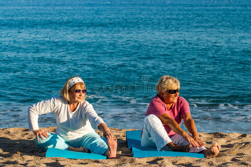 Two golden age ladies stretching on beach. royalty free stock photography