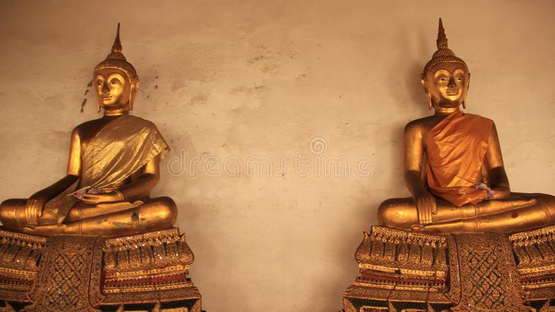 Two Golden Buddhas Image On Gilded Stucco Bench. Religion. Golden Buddhas Image symbol and traditional of Buddhism with silk clothing in Bangkok Thailand royalty free stock photography