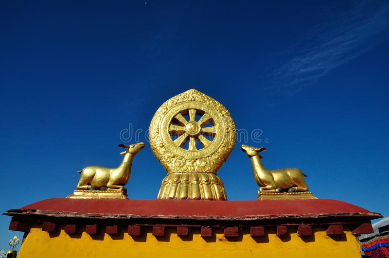 Two golden deer flanking a Dharma wheel on Jokhang. The rooftop statues of two golden deer flanking a Dharma wheel on the Jokhang.The Jokhang , also called the stock photos