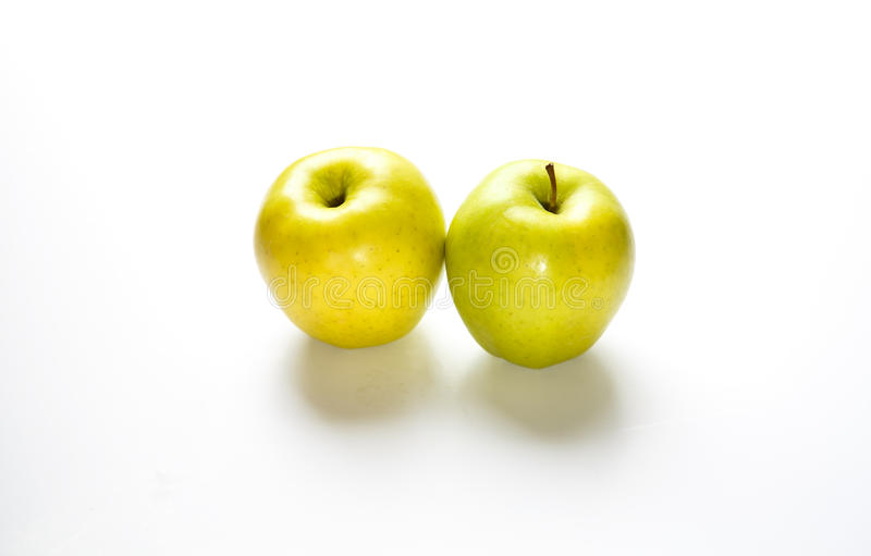 Two Golden Delicious Apples on White Counter stock images
