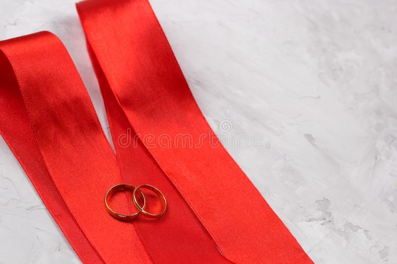 Two golden rings and red satin ribbon stock images