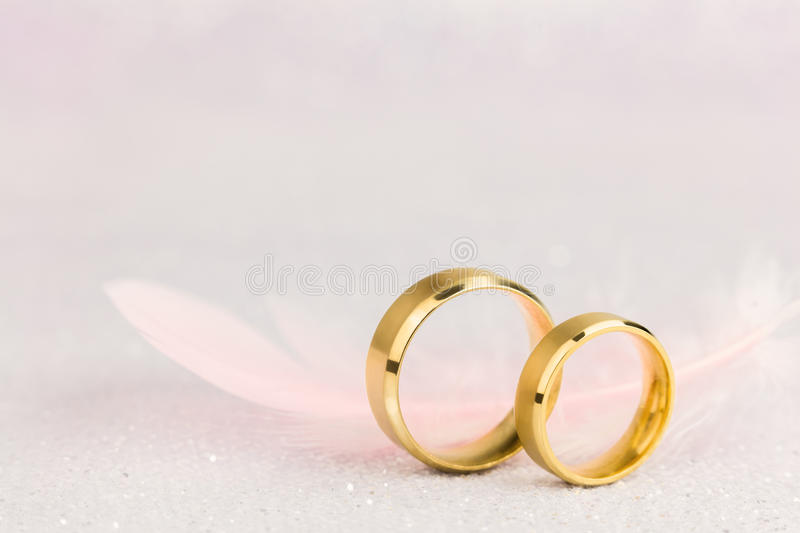 Two Golden Wedding Rings and Light Angel Feather stock images