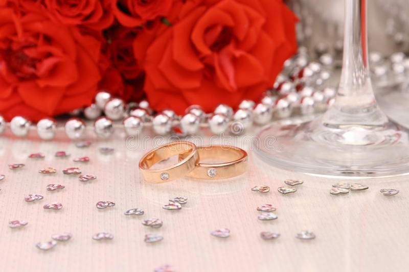 Two golden wedding rings with red roses stock photo