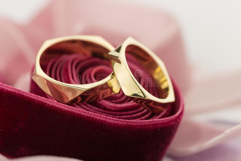 Two golden wedding rings on red velvet ribbon stock images