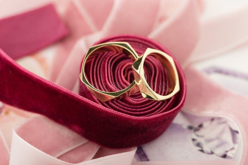 Two golden wedding rings on red velvet ribbon royalty free stock images