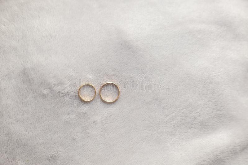 Two golden wedding rings on top of a soft gray fabric as a background stock images