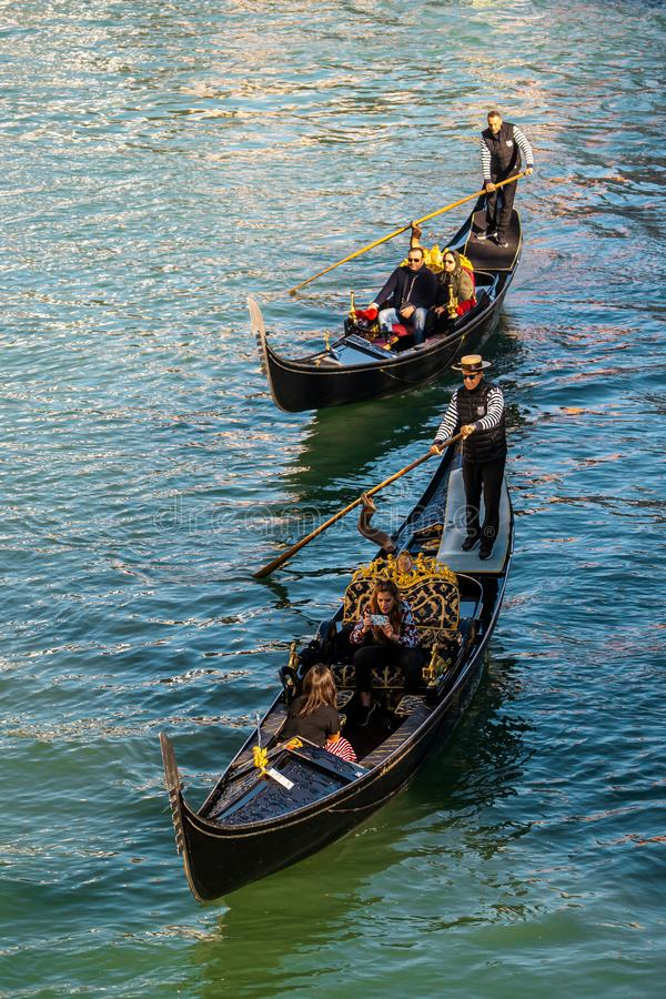 Two gondolas with tourists around grand canal  in the evening before autumn in Venice , Italy royalty free stock photos