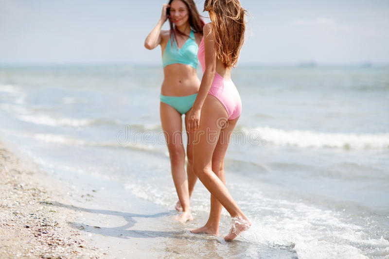Two good-looking young girls in colorful swimsuits on a sea background. Ladies walking along a beach. Copy space. stock images