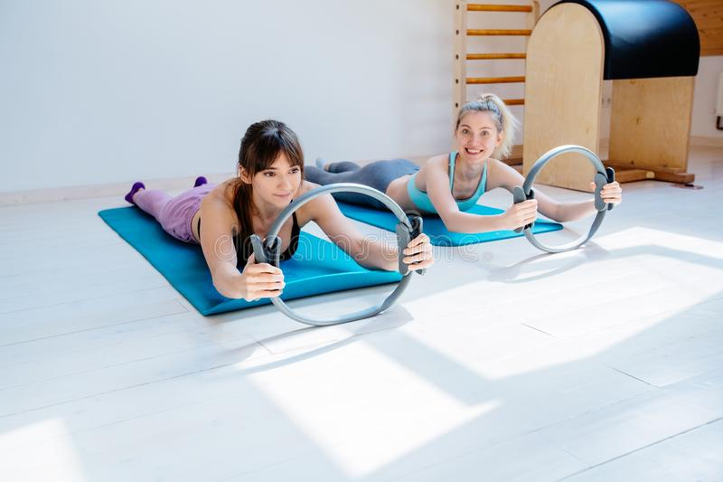 Two gorgeous fitness women exercising with pilates ring lying on blue mat in studio with pilates equipment on background royalty free stock photography