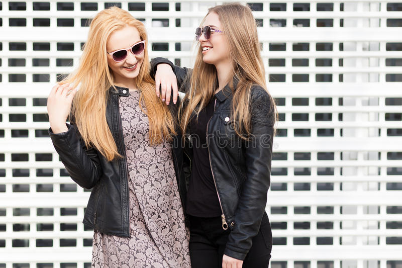 Two gorgeous girl friends having fun outside in the city. Friendship and urban lifestyle stock image