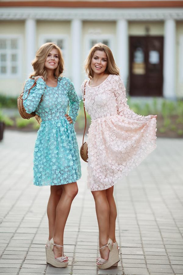 Pretty girls in rose and blue flowery dresses posing and smiling. royalty free stock images