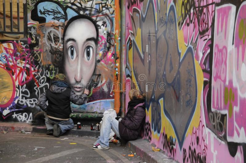 Two graffiti artists at work. Streeti artists putting the finishing touches to a graffiti on a wall of the Undercroft, London,Uk royalty free stock photography