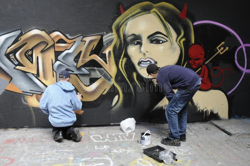 Two graffiti artists at work. Streeti artists putting the finishing touches to a graffiti on a wall of the Undercroft, London,Uk stock image