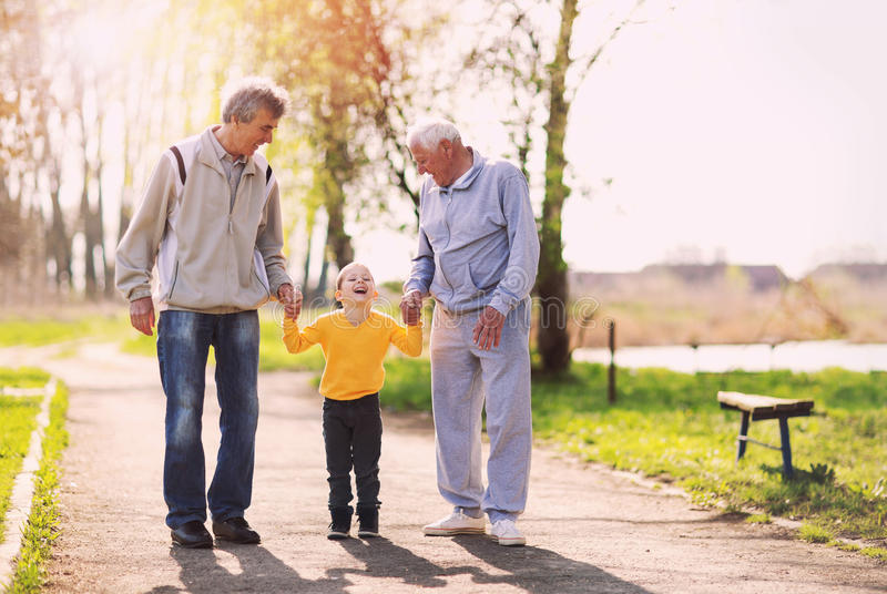 Two grandfather walking with the grandson royalty free stock photos