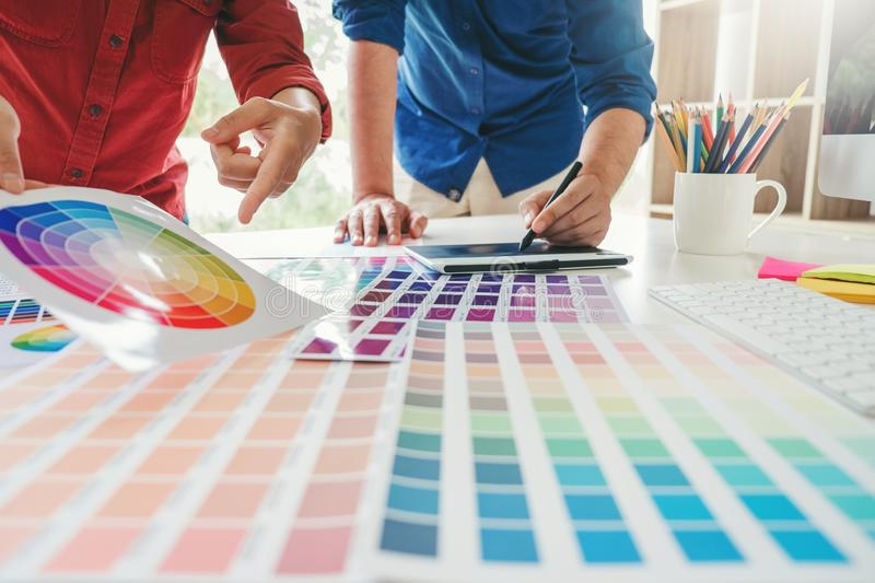 Two Graphic designer drawing on graphics tablet and color palette guide at workplace.  royalty free stock images